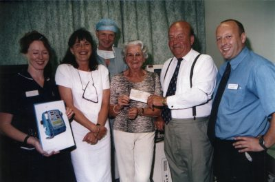 Helen Liwicki receiving funds raised at a 2002 barbeque.